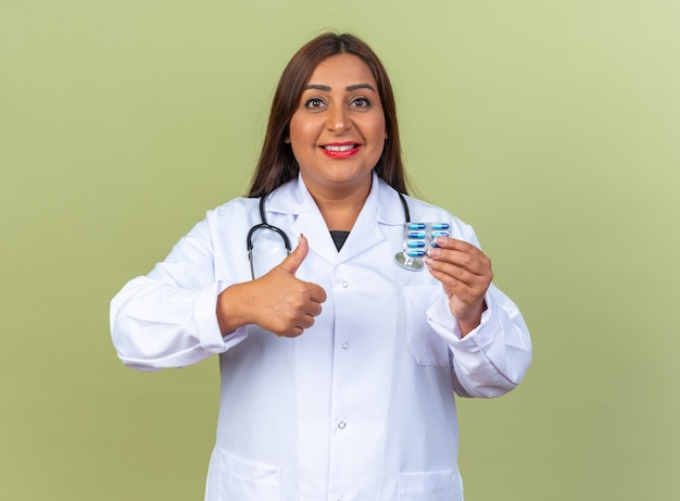 Femme médecin d'âge moyen en blouse blanche avec stéthoscope holding blister with pills showing thumbs up smiling confiant standing on green