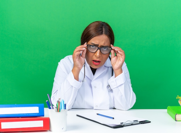 Femme médecin d'âge moyen en blouse blanche avec stéthoscope portant des lunettes confuse et très anxieuse assise à la table sur un mur vert