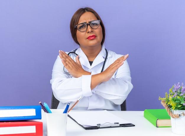 Femme médecin d'âge moyen en blouse blanche avec stéthoscope portant des lunettes regardant à l'avant avec un visage sérieux faisant un geste d'arrêt croisant les mains assis à la table sur le mur bleu