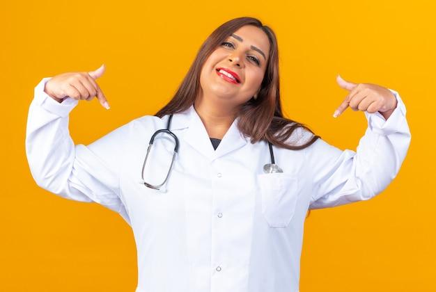 Femme médecin d'âge moyen en blouse blanche avec stéthoscope souriant confiant, heureux et positif se montrant debout sur un mur orange