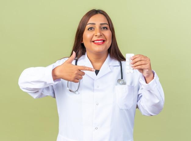 Femme médecin d'âge moyen en blouse blanche avec stéthoscope tenant un blister avec des pilules pointant avec l'index sur des pilules souriant joyeusement debout sur un mur vert