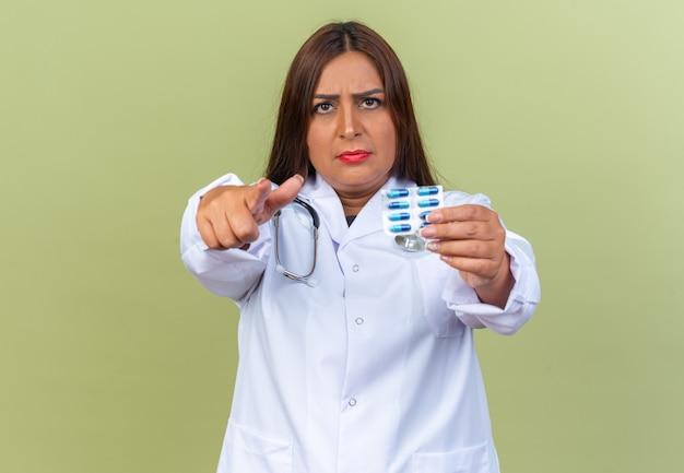 Femme médecin d'âge moyen en blouse blanche avec stéthoscope tenant un blister avec des pilules pointant avec l'index à la recherche d'un visage sérieux debout sur le vert