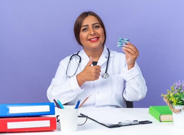 Femme médecin d'âge moyen en blouse blanche avec stéthoscope tenant des pilules regardant devant un sourire heureux et positif montrant les pouces vers le haut assis à la table sur le mur bleu