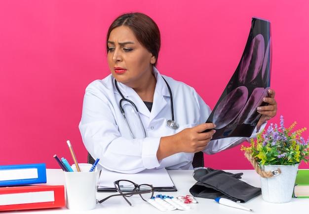 Femme médecin d'âge moyen en blouse blanche avec stéthoscope tenant une radiographie regardant de côté confuse et très anxieuse assise à la table avec des dossiers de bureau sur rose