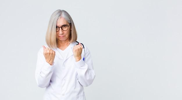 Femme médecin d'âge moyen à la confiance, en colère, forte et agressive, avec les poings prêts à se battre en position de boxe