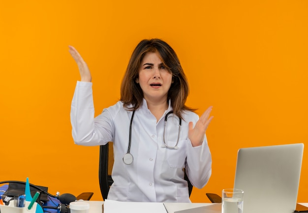 Femme médecin d'âge moyen confus portant une robe médicale avec stéthoscope assis au bureau de travail sur un ordinateur portable avec des outils médicaux levant la main sur un mur orange isolé avec espace de copie