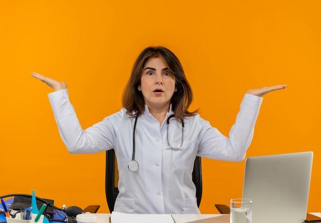 Femme médecin d'âge moyen confus portant une robe médicale avec stéthoscope assis au bureau de travail sur un ordinateur portable avec des outils médicaux se propage les mains sur un mur orange isolé avec espace de copie