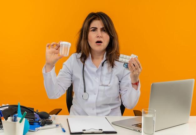 Femme médecin d'âge moyen confus portant une robe médicale avec stéthoscope assis au bureau de travail sur un ordinateur portable avec des outils médicaux tenant une boîte vide et des pilules sur un mur orange isolé