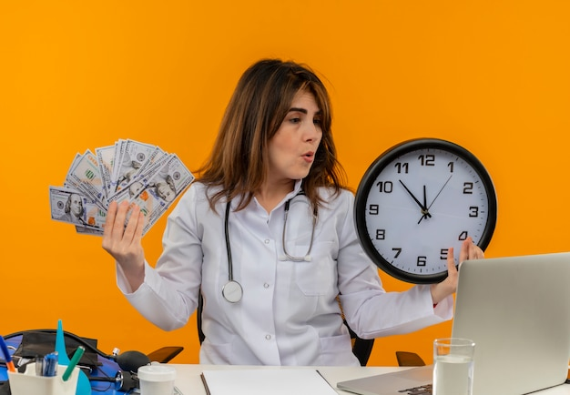 Femme médecin d'âge moyen confus portant une robe médicale avec stéthoscope assis au bureau de travail sur un ordinateur portable avec des outils médicaux tenant une horloge murale et de l'argent sur un mur orange isolé avec espace de copie