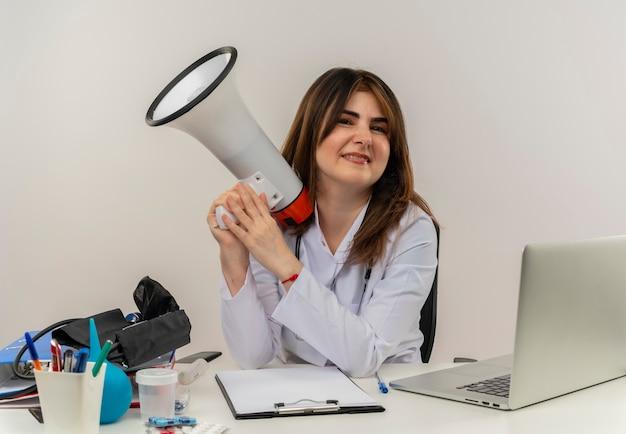 Femme médecin d'âge moyen portant une robe médicale avec stéthoscope assis au bureau de travail sur ordinateur portable avec des outils médicaux tenant haut-parleur sur mur blanc avec espace copie