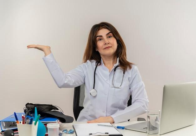 Femme médecin d'âge moyen portant une robe médicale avec stéthoscope assis au bureau de travail sur un ordinateur portable avec des points d'outils médicaux avec la main à l'autre sur un mur blanc avec espace de copie