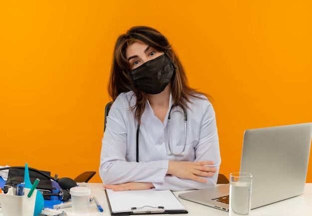 Femme médecin d'âge moyen portant une robe médicale avec stéthoscope en masque médical assis au bureau de travail sur un ordinateur portable avec des outils médicaux sur un mur orange isolé avec espace de copie