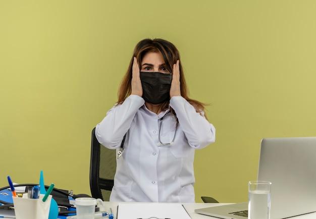 Femme médecin d'âge moyen portant une robe médicale avec stéthoscope en masque médical assis au bureau de travail sur un ordinateur portable avec des outils médicaux a saisi la tête sur le mur vert avec espace de copie