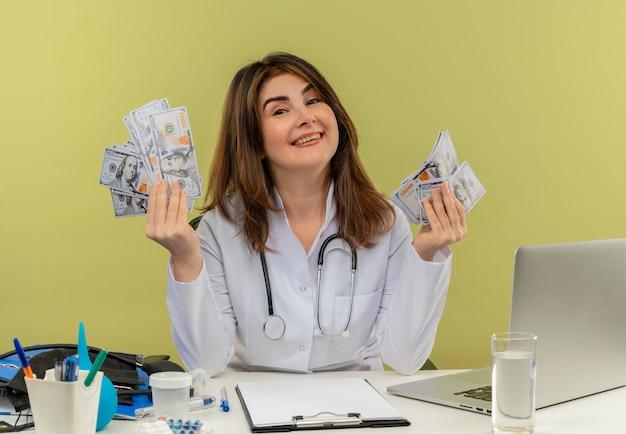 Femme médecin d'âge moyen souriant portant une robe médicale avec stéthoscope assis au bureau de travail sur un ordinateur portable avec des outils nedical tenant de l'argent avec copie espace