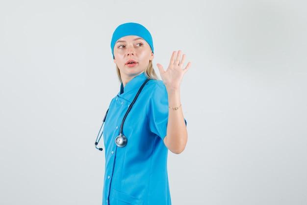 Femme médecin en agitant la main tout en regardant en arrière en uniforme bleu.