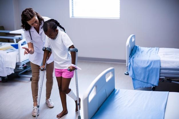 Femme médecin aidant la fille à marcher avec des béquilles en salle