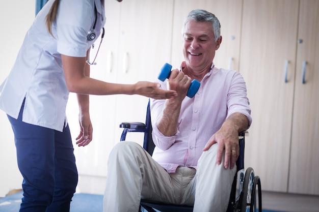 Femme médecin aidant l'homme senior à soulever des haltères