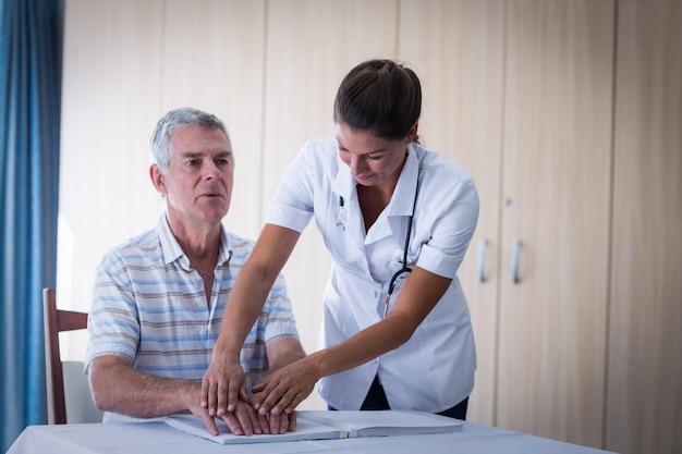 Femme médecin aidant le patient à lire le livre en braille