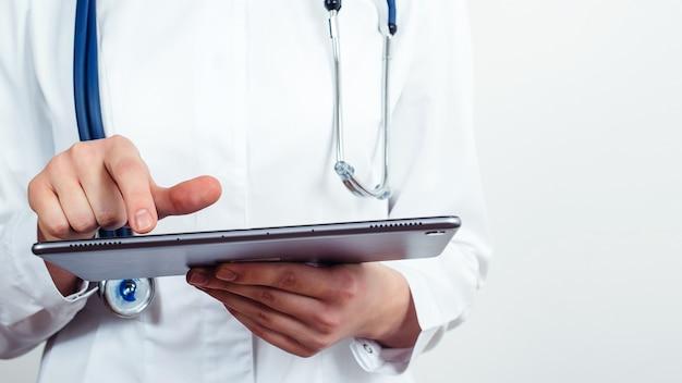 Femme médecin à l'aide d'un ordinateur tablette. médecin debout à l'hôpital. médecin lisant le rapport du patient.