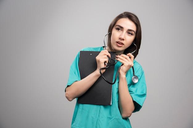 Femme médecin à l'aide d'un stéthoscope sur fond gris. photo de haute qualité