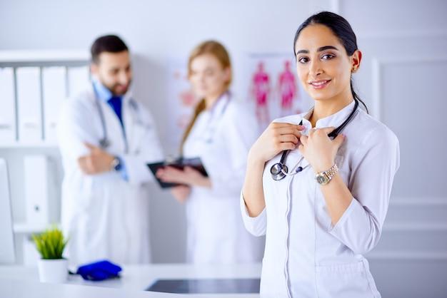 Femme médecin arabe souriant avec stéthoscope debout devant son équipe à l'hôpital