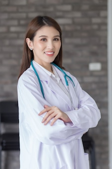 Femme médecin asiatique debout avec les bras croisés heureux et souriant à l'hôpital