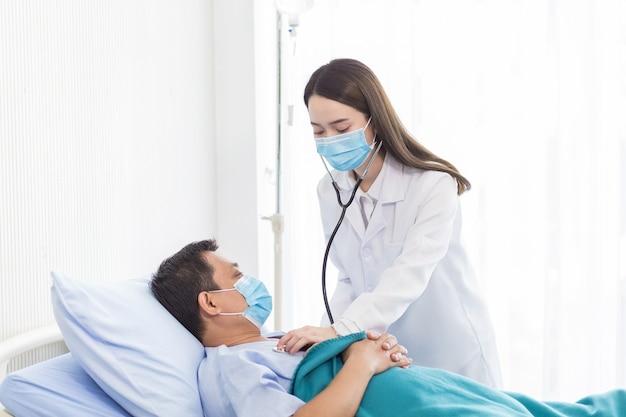 Une femme médecin asiatique examinant un homme dans un lit d'hôpital pour un examen