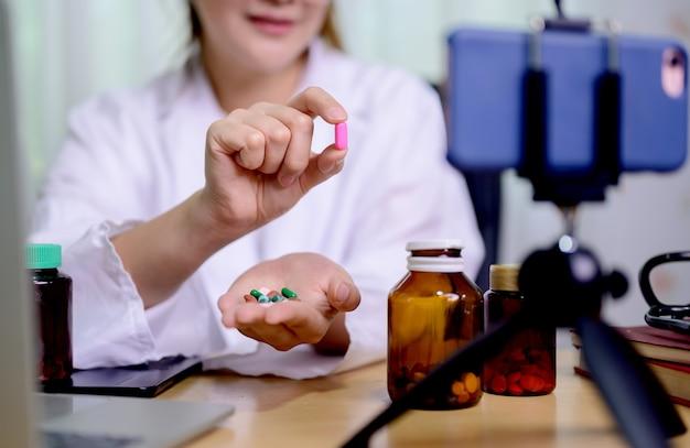 Femme médecin asiatique en ligne travaillant à la maison. enregistrement d'une vidéo de blog pour prendre des médicaments et des soins de santé.