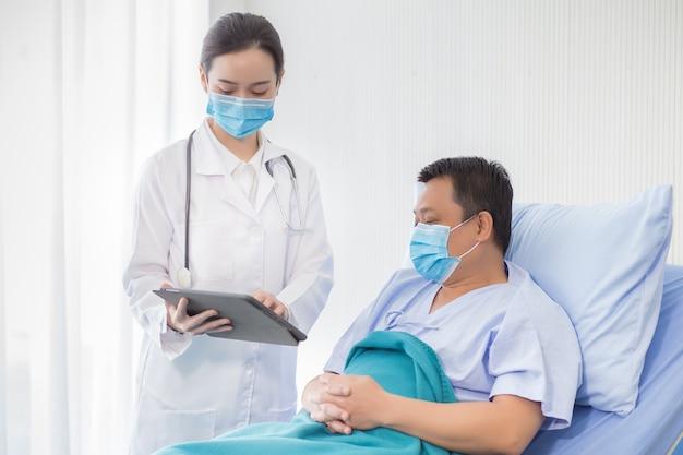 Femme médecin asiatique parlant avec un patient homme qu'il est au lit à propos de sa douleur et de ses symptômes