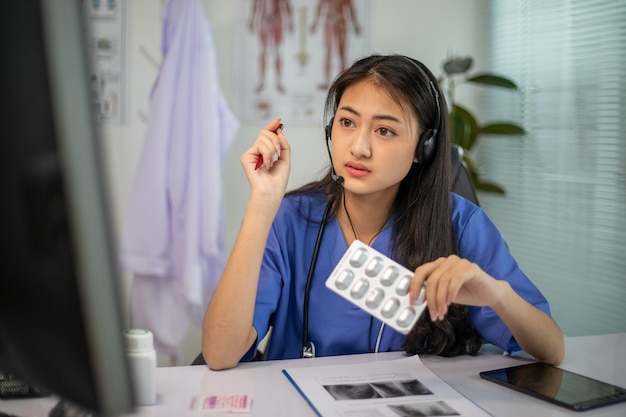 Une femme médecin asiatique parle par chat vidéo et consulte un patient en ligne sur les symptômes et les médicaments