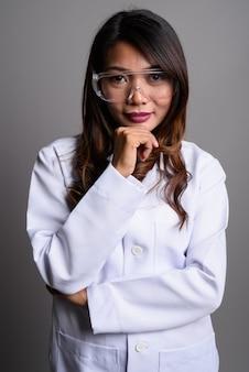 Femme médecin asiatique portant des lunettes de protection contre backg gris