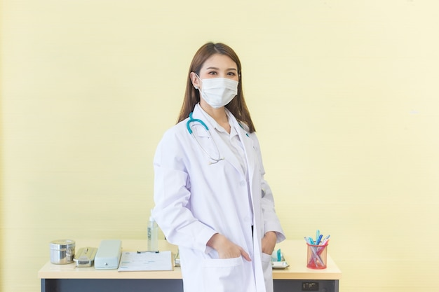 Une femme médecin asiatique qui a les cheveux longs noirs porte un masque médical et porte un stéthoscope