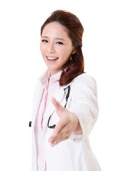 Femme médecin asiatique sympathique, serrer la main avec vous, portrait agrandi isolé sur un mur blanc.