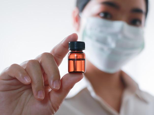 Femme médecin asiatique tenant un flacon de médicament pour injection.