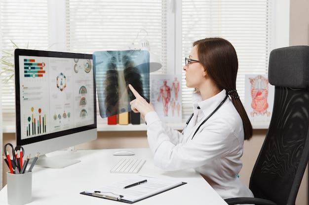 Femme médecin assise au bureau, travaillant sur ordinateur, tenant une radiographie des poumons, fluorographie, roentgen dans un bureau léger à l'hôpital