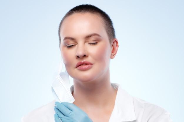 Femme médecin aux cheveux courts en robe médicale enlevant son masque