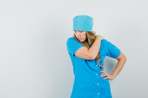 Femme médecin ayant des douleurs à l'épaule en uniforme bleu et à la recherche d'inconfort