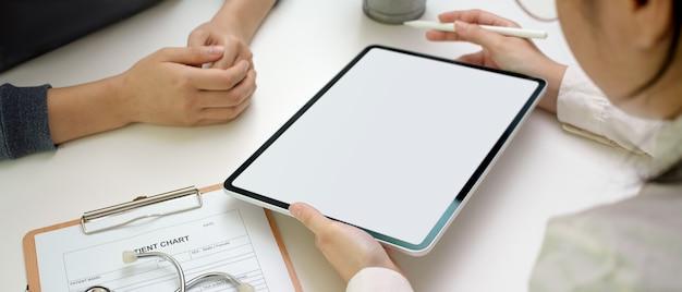 Femme médecin bilan médical patiente tout en regardant le dossier médical sur la tablette écran vide