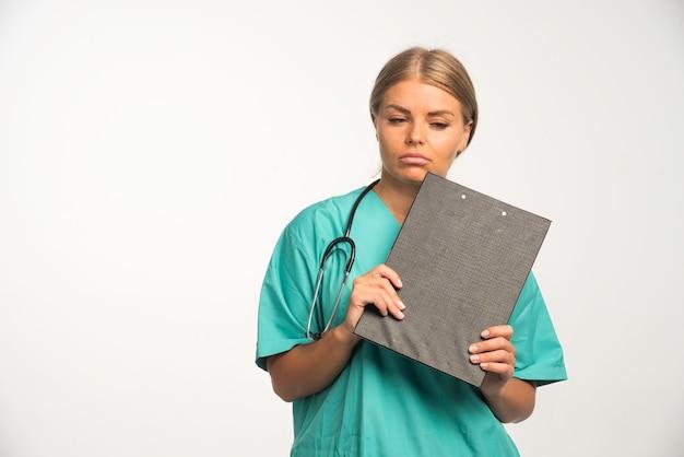 Femme médecin blonde en uniforme bleu tenant un livre de reçus et rêvant.