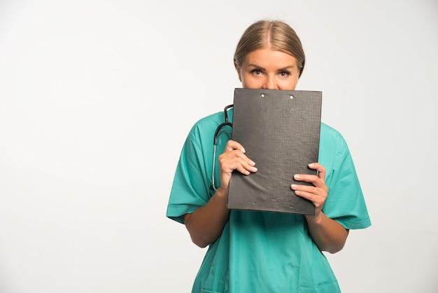 Femme médecin blonde en uniforme bleu tenant un livre de reçus et se cachant derrière.