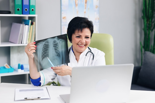 Femme médecin en blouse blanche faisant une conférence téléphonique sur un ordinateur portable consultant à distance un patient en ligne dans un chat vidéo, explique le traitement par le concept de webcam