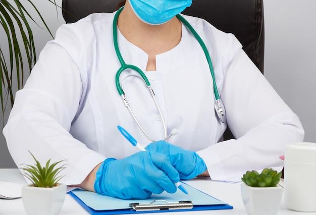 Femme médecin en blouse blanche, gants médicaux stériles écrit une ordonnance sur un formulaire