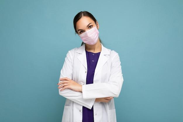 Femme médecin en blouse blanche et masque médical debout isolé