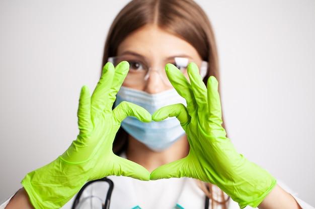 Femme médecin en blouse blanche montre à la main un signe cardiaque