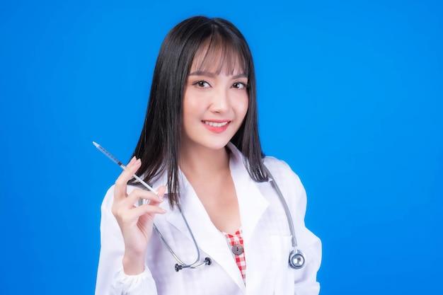 Femme médecin en blouse médicale blanche stérile avec stéthoscope tenant une seringue pour la vaccination contre le virus coronavirus covid-19 isolé sur fond bleu - protéger la propagation du virus corona covid19