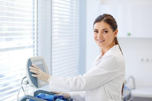 Femme médecin boutons-poussoirs sur l'équipement médical, aime travailler à l'hôpital, souriant. utiliser des équipements modernes pour le traitement en clinique. concept de médecine et de soins de santé