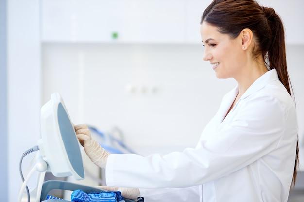 Femme médecin boutons-poussoirs sur l'équipement médical, aime travailler à l'hôpital. utiliser des équipements modernes pour le traitement en clinique. concept de médecine et de soins de santé. vue de côté