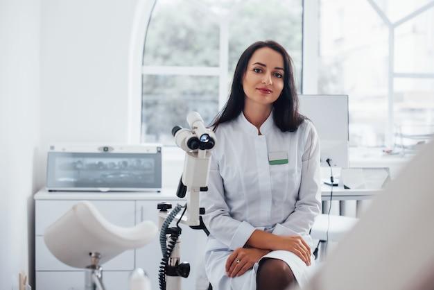 Une femme médecin brune est assise dans un bureau moderne par ordinateur et regarde la caméra.