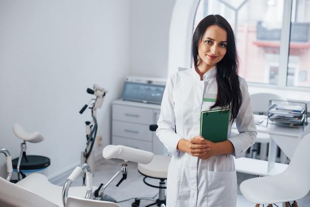 Une femme médecin brune se tient dans un bureau moderne et regarde la caméra.