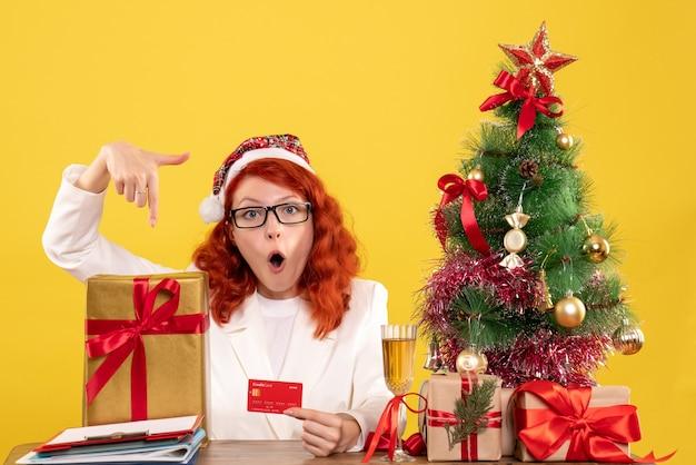 Femme médecin avec cadeau et carte bancaire sur jaune clair